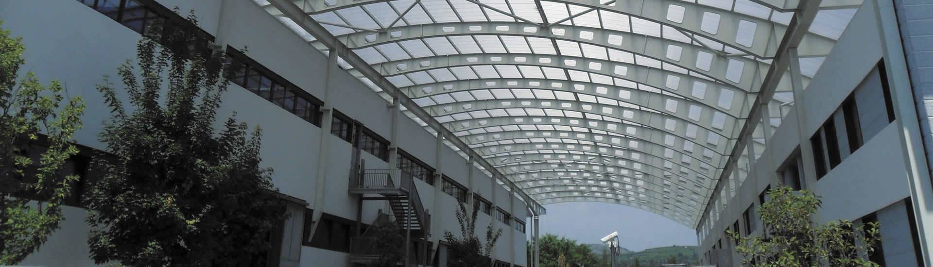Frosted polycarbonate sheets are covering the space between two building.