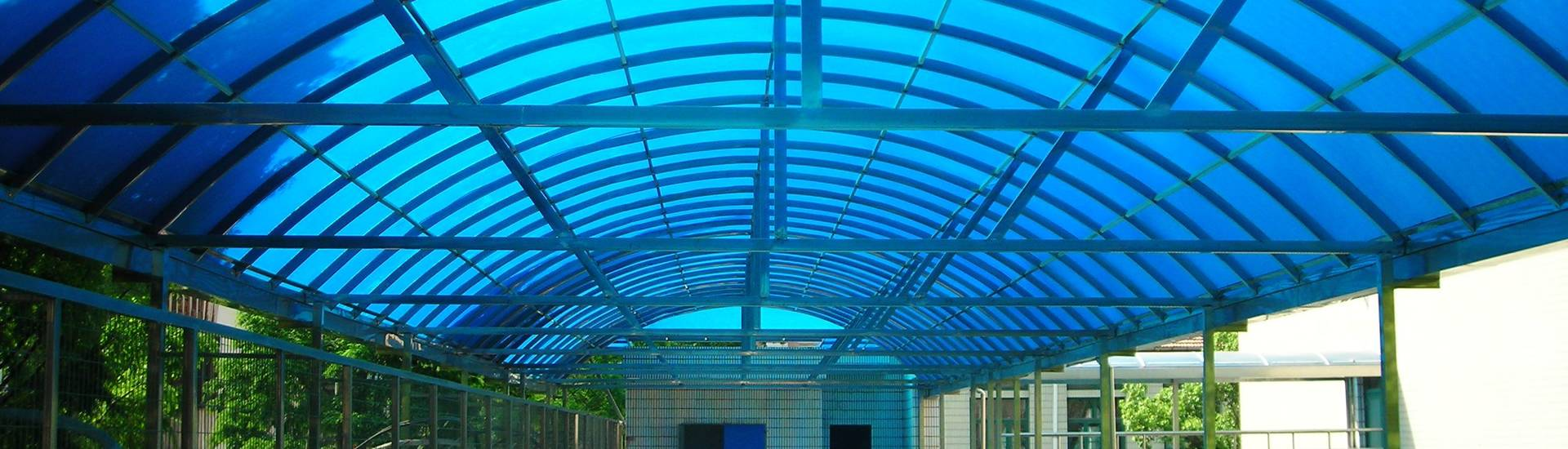 Blue and green twin wall polycarbonate sheets are covering the side of railway for shelter.